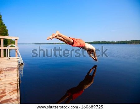 Young man jumping into water - stock photo
