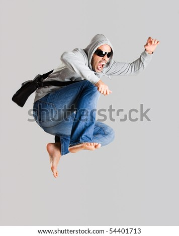 Young man jumping isolated over a gray background