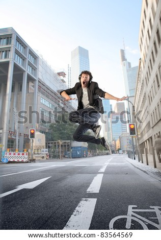 Young man jumping on a city street - stock photo
