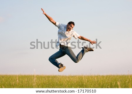 Young man jumping on a meadow - stock photo