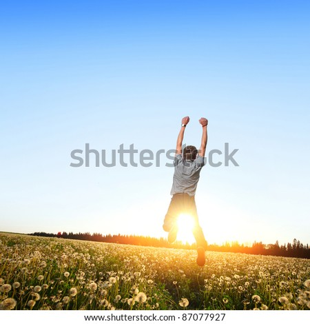 Young man jumping on a meadow with dandelions - stock photo