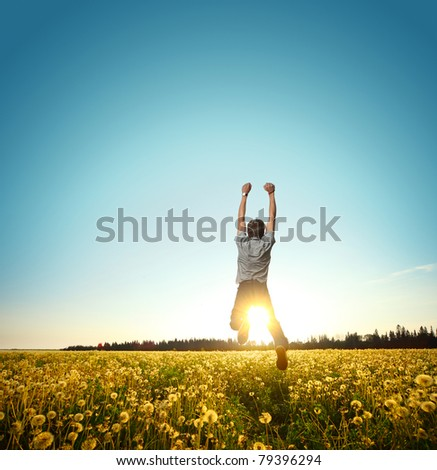Young man jumping on meadow with dandelions on clear blue sky background - stock photo