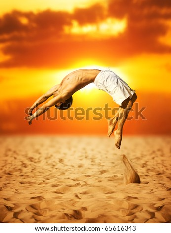 Young man jumping. On sunset background. - stock photo