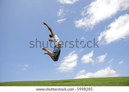 Young man jumping very high on a green meadow