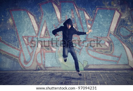 Young man jumping with a graffiti in the background - stock photo