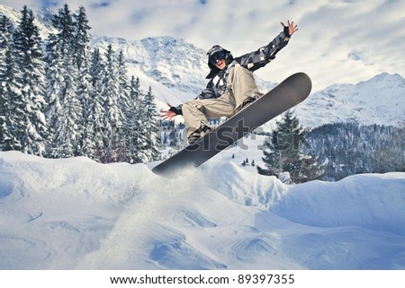 Young man jumping with a snowboard in the mountains - stock photo