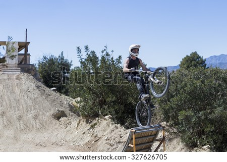 young man jumping with BMX bike using a ramp on a BMX session in the mountain - focus on the body - stock photo