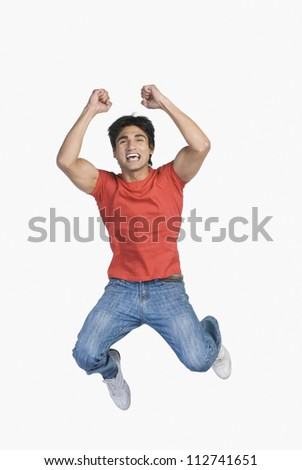 Young man jumping with raised arms - stock photo