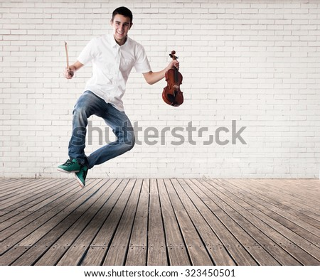 young man jumping with violin on a room - stock photo