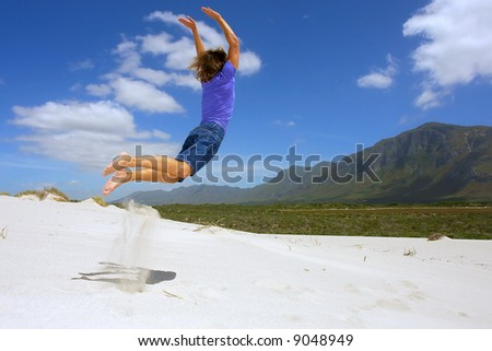 Young man jumps from sand dune towards awesome mountains. Shot in Hermanus, Walker Bay, Western Cape, South Africa.