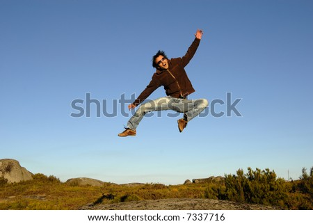 young man jumps high in the mountain