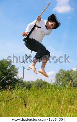 young man jumps with guitar on grass - stock photo