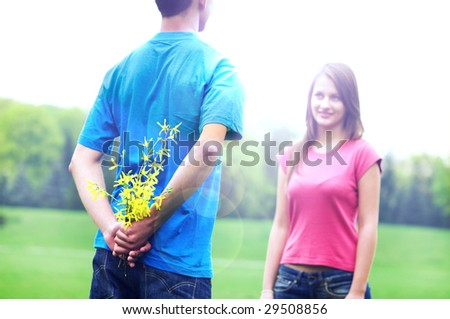 Young man just before giving flowers to her girlfriend - stock photo