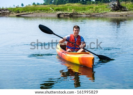 Young Man Kayaking Alone on a Calm River and Wearing a Safety Vest - stock photo