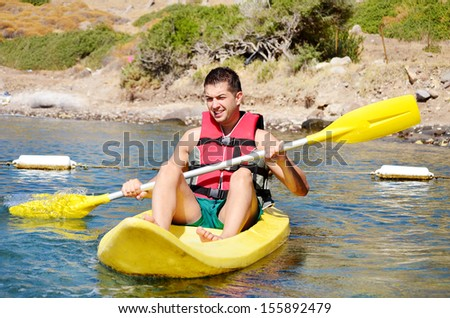 young man kayaking in the sea - stock photo