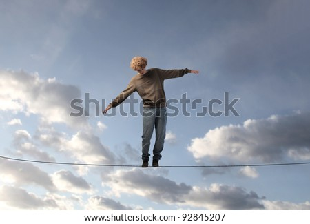 Young man keeping his balance on a cable - stock photo