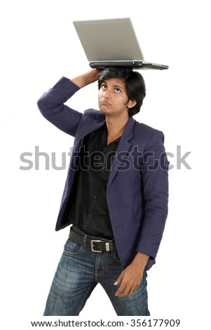 young man keeping  laptop on his head like showing his overload - stock photo