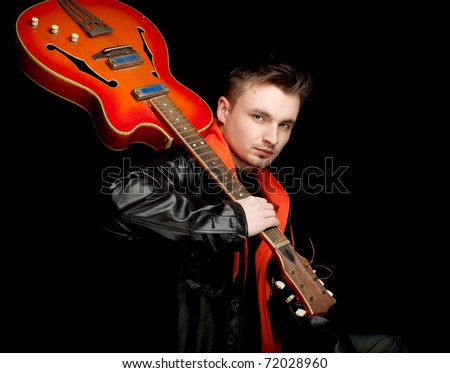 young man keeping orange electric guitar, black background