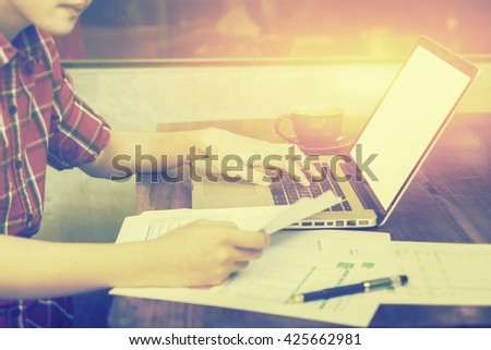 young man keyboarding on laptop computer with blank copy space screen while sitting in cafe, male student working on net-book after her lectures in University,vintage color,selective focus - stock photo