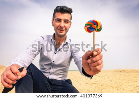 Young man kidnapper with evil face offering lollipop to children on secluded beach - Handsome parent giving lollies to little kid - Concept of pedophilia and kidnapping danger to children left alone - stock photo