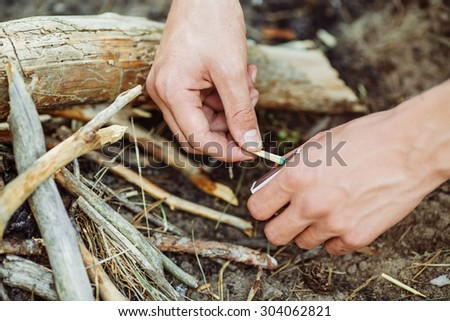 young man kindles a fire in summer wood - stock photo