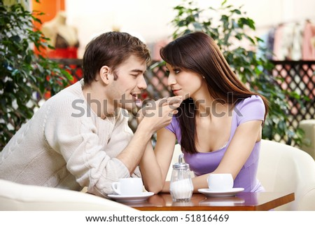 Young man kisses a hand to the beautiful girl on cafe - stock photo