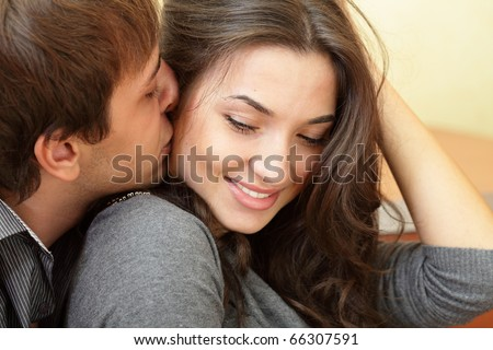 Young man kisses his beautiful girlfriend - stock photo