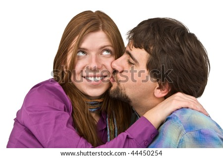 Young man kissing a confused girl isolated on white.
