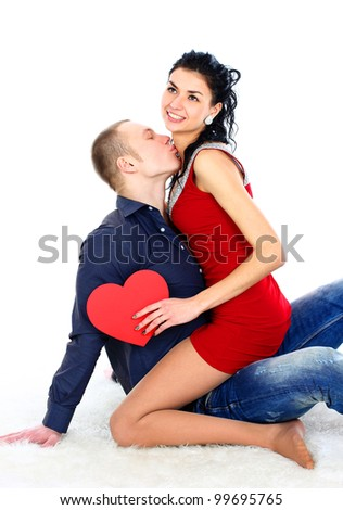 Young man kissing a pretty girl in a Valentine's Day, sitting on the floor
