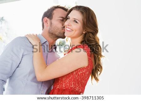 Young man kissing beautiful woman on cheek - stock photo