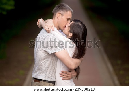 Young man kissing his beautiful girlfriend, attractive couple of lovers standing in park in summer on a date, embracing outdoors - stock photo