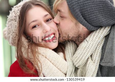Young man kissing his girlfriend - stock photo