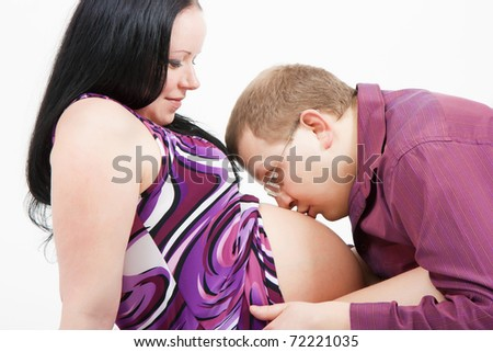 young man kissing the stomach pregnant wife