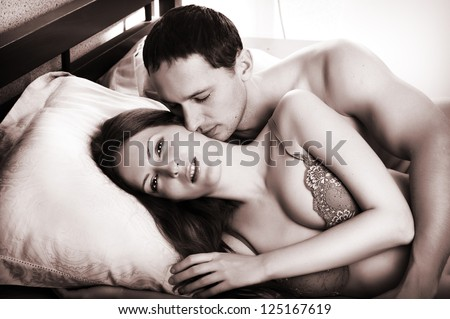 Young man kissing woman in darkness bedroom on bed