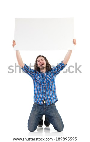 Young man kneeling on the floor and holding a placard over his head. Full length studio shot isolated on white.