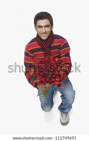 Young man kneeling with a bouquet of flowers - stock photo
