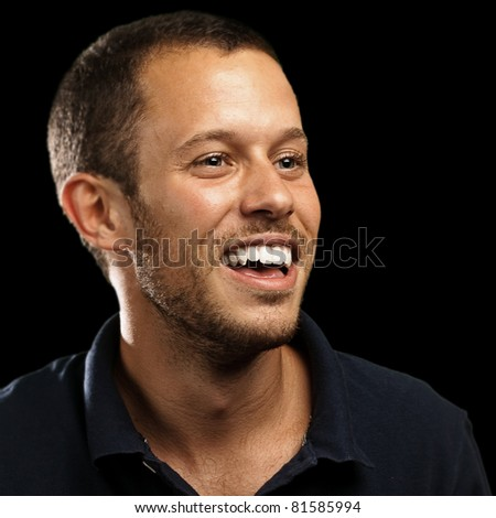 young man laughing against a black background