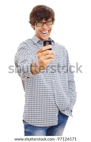 Young man laughing and filming something funny on his mobile phone. Isolated on white background, mask included - stock photo