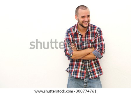 Young man laughing and looking away standing against white background with arms crossed - stock photo