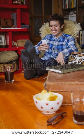 Young man laughing and looking smartphone sitting on a chair at home. Teenager leisure time concept. - stock photo