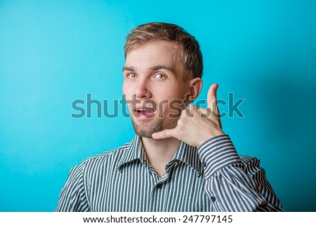 Young man . Laughing shows call me. gesture. photo shoot. - stock photo