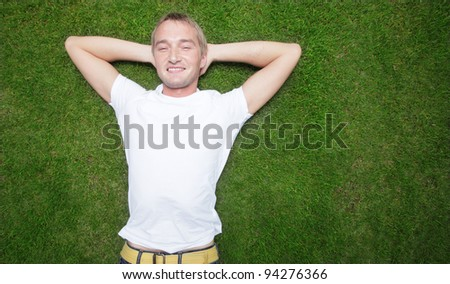 Young man laying on green grass - stock photo