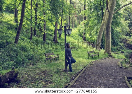 Young man leaning against an old street lamp in a park. Concept for grief or sadness - stock photo