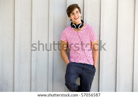 Young man leaning against wall - stock photo