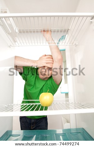 Young man leaning in open doorway of open refrigerator with single apple on empty shelves. - stock photo