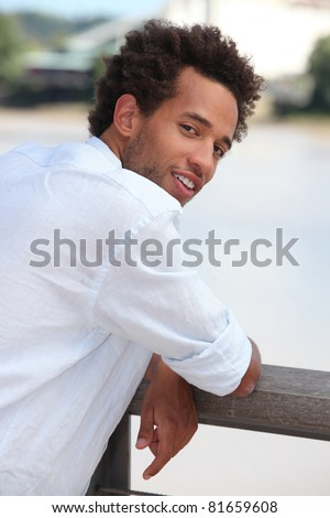Young man leaning on a wooden fence - stock photo