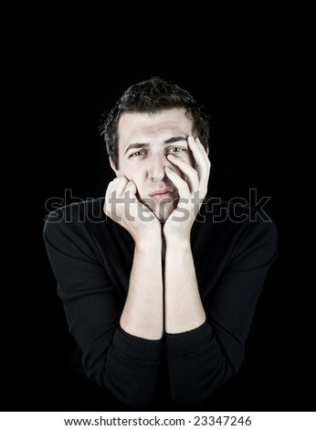 young man leaning on his hands looking bored/skeptical on black - stock photo