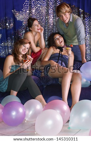 Young man leaning over sofa enjoying attention of women at social event - stock photo