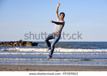 Young man leaping in air at beach, blue sky and ocean in the background - stock photo