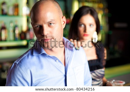 young man leaving bar ad woman holding him by the shoulder - stock photo